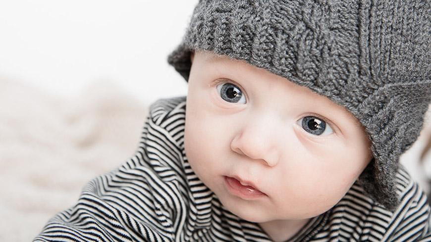 Babyfoto-Newborn mit Mütze fotografiert vom Fotograf/Fotostudio