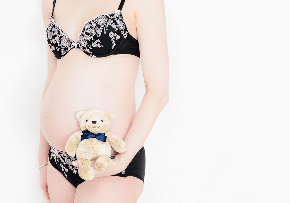 Schwangerschaftsfoto-Babybauchfoto, Unterwäsche mit Teddy, fotografiert vom Fotograf/Fotostudio
