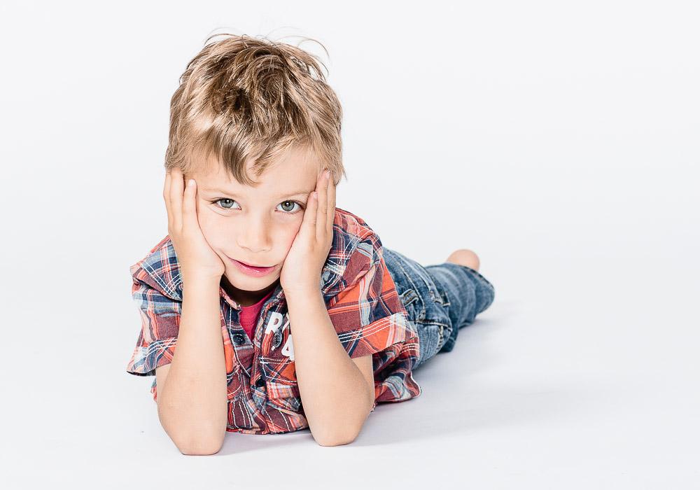 Kinderfoto mit Junge liegend, fotografiert vom Fotograf/Fotostudio